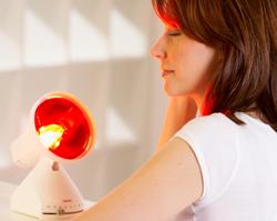 Donna che usa una lampada a infrarossi